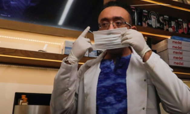 """Dr. Wael Abd Elaziz wears a protective mask in """"Dawa Pharmacy"""" the first Egyptian pharmacy using a robotic device that handles prescriptions, due to outbreak of the coronavirus disease, in Cairo, (Reuters)"""