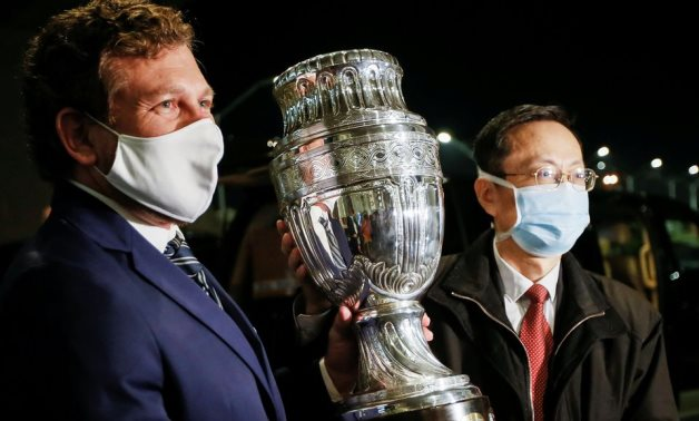 Alejandro Dominguez, president of CONMEBOL, with Chinese Ambassador to Uruguay Wang Gang hold the Copa America trophy, Reuters