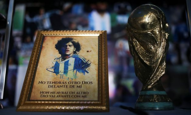 A picture of Diego Maradona and a replica of the World Cup trophy are pictured on an altar at the first Mexico's church, Reuters