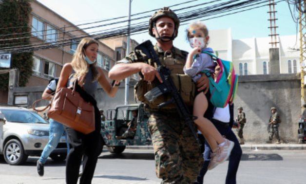 Lebanese soldier carrying a schoolgirl after the shooting - Mohamed Azakir/Reuters