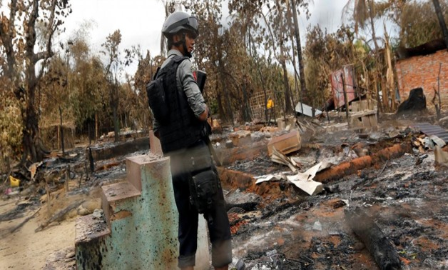 A police officer stands in a house that was burnt down during the days of violence in Maungdaw, Myanmar August 30 2017 - RETUERS.png