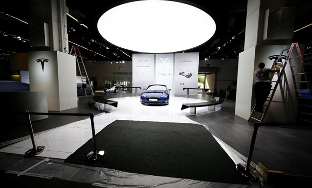 FILE PHOTO: People run preparations at the Tesla company booth during the media day at the Frankfurt Motor Show (IAA) in Frankfurt, Germany, September 14, 2015. REUTERS/Kai Pfaffenbach/File Photo