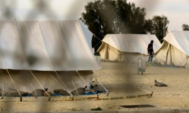 A Syrian refugee walks between tents at a reception centre in Kokkinotrimithia outide the Cypriot capital Nicosia on March 7, 2017