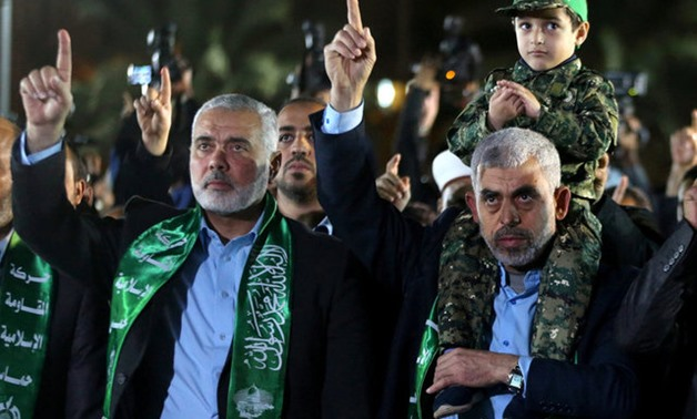The son of senior Hamas militant Mazen Fuqaha sits on the shoulders of Hamas Gaza Chief Yahya Al-Sinwar as Hamas leader Ismail Haniyeh (L) gestures during a memorial service for Fuqaha, in Gaza City March 27, 2017. REUTERS/Mohammed Salem/File Photo