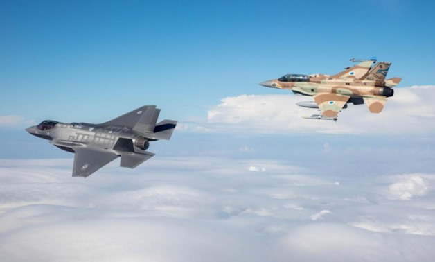 One of Israel's first two F-35 stealth fighter jets flies alongside an F-16 on its maiden flight as part of the Israeli Air Force on December 13 - Press photo