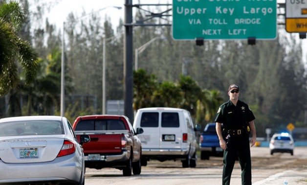 A police officer stands on the entry road for the Florida Keys road after Hurricane Irma strikes Florida, in Homestead - REUTERS