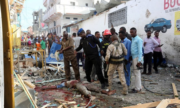 Somali security forces look at the dead body of a man killed after car exploded in Al Mukaram street in Mogadishu - REUTERS