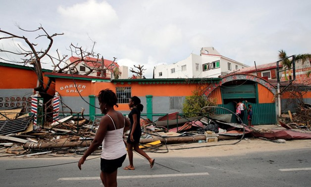 Residents walk in front of houses destroyed by Hurricane Irma during the visit of France's President Emmanuel Macron in the French Caribbean islands of St. Martin September 12, 2017. REUTERS/Christophe Ena/Pool