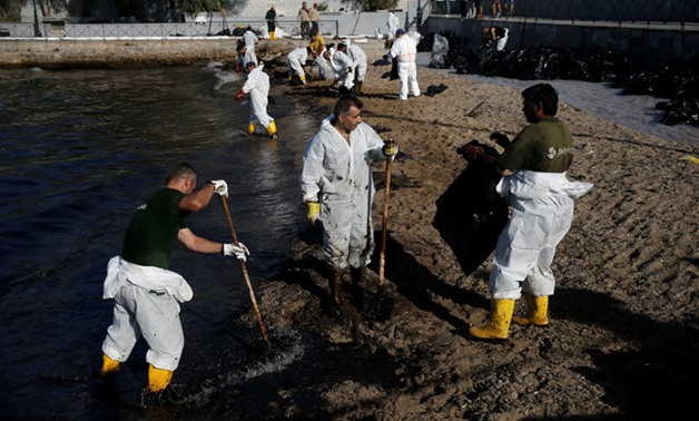 Workers clean a beach covered with oil that leaked from a small oil tanker that sank on September 10 off the shores of Salamina island, at the suburb of Faliro in Athens - REUTERS