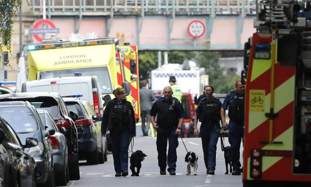 Police officers walk with dogs after an incident at Parsons Green underground station in London - REUTERS
