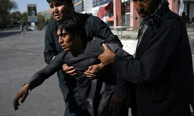 Shiites carry a wounded friend after a suicide attack on a mosque in Kabul on August 25, 2017-AFP