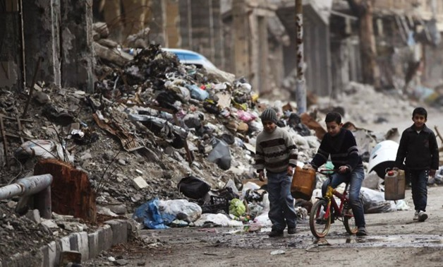 Boys walk along a street covered with garbage and rubble in Deir al-Zor - REUTERS