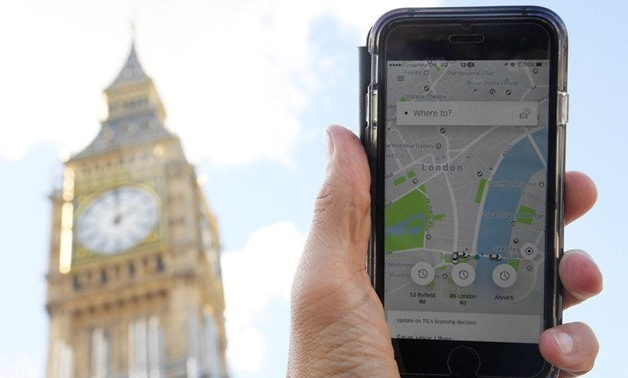 A photo illustration shows the Uber app on a mobile telephone, as it is held up for a posed photograph in central London, Britain - Reuters/Toby Melville
