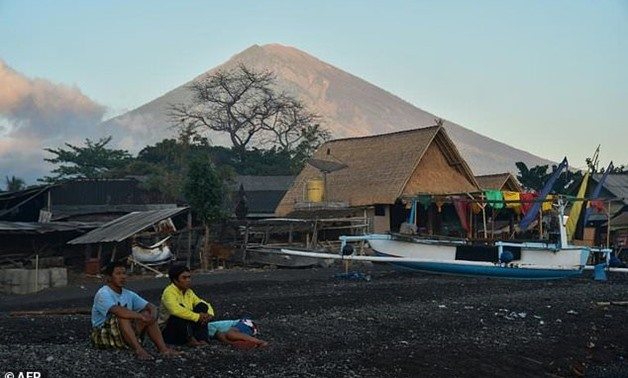 Locals sit near huts and fishing boats on Amed beach, one of the tourist resorts nearest to the Mount Agung volcano, on the island of Bali -AFP