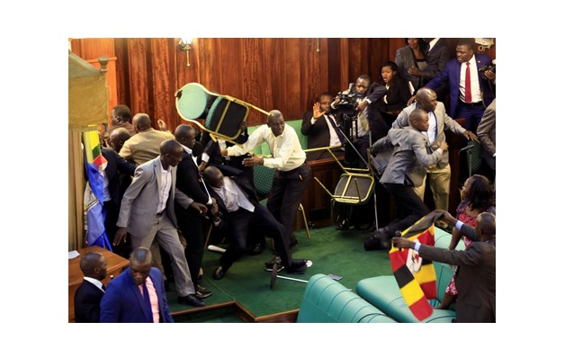 Ugandan opposition lawmakers fight with plain-clothes security personnel in the parliament while protesting a proposed age limit amendment bill debate to change the constitution for the extension of the president's rule, in Kampala, Uganda September 27, 2