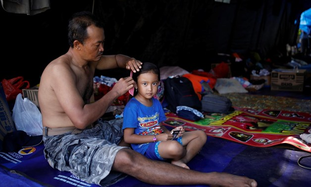 A man combs his daughter's hair inside a tent at a temporary evacuation center for people living near Mount Agung, a volcano on the highest alert level, in Manggis, on the resort island of Bali, Indonesia, September 28, 2017. REUTERS/Darren Whiteside