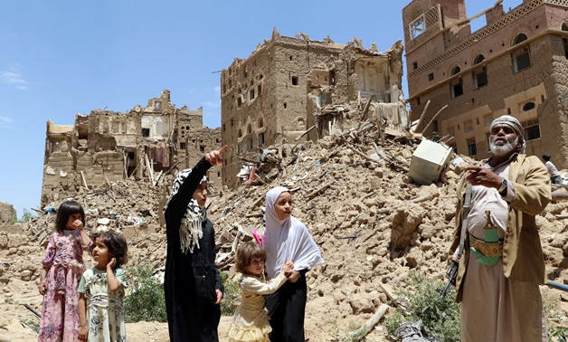 People stand past houses destroyed in an outskirt of the northwestern city of Saada, Yemen September 5, 2017. REUTERS/Naif Rahma