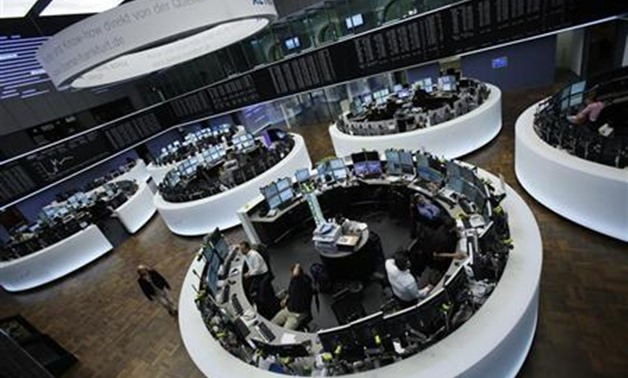 Traders work at their desks in front of the DAX board at the Frankfurt stock exchange - REUTERS