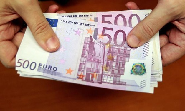 FILE PHOTO: A bank employee holds a pile of 500 euro notes at a bank branch in Madrid January 13, 2011. REUTERS-Andrea Comas-File Photo