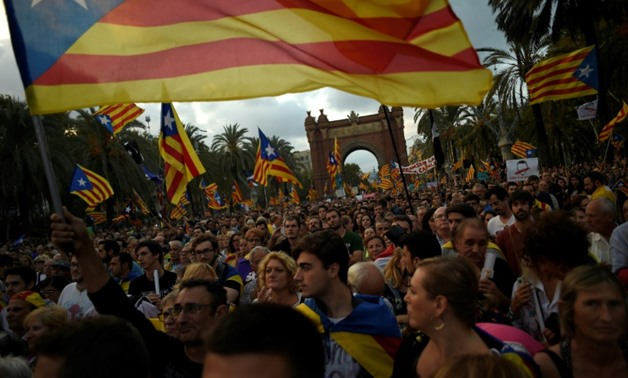 Thousands gathered outside the parliament building in Barcelona on Tuesday evening, waving Catalan flags and banners screaming 'democracy' in the hope of witnessing a historic night in a region that remains deeply divided over independence -AFP