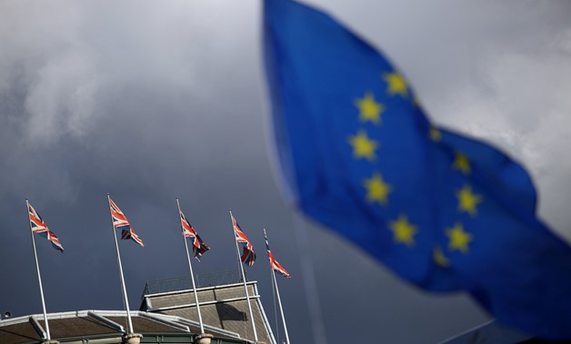 A European Union flag flies in front of Union Jack flags in London, Britain, September 13, 2017. REUTERS/Hannah McKay