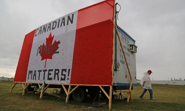 """A striking member of the auto workers union Unifor walks to a picket line past a trailer covered by with a Canadian flag reading """"Canadian Made Matters!"""", outside the General Motors Company (GM) CAMI assembly plant in Ingersoll, Ontario, Canada October 13"""