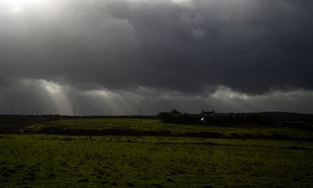 Rays of sunlight shine through dark clouds as storm Ophelia hits the County Clare town of Doonbeg, Ireland October 16, 2017. REUTERS/Clodagh Kilcoyne