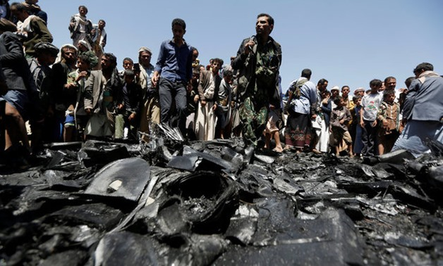 People gather at the site of the wreckage of a drone aircraft which the Houthi rebels said they have downed in Sanaa -- REUTERS
