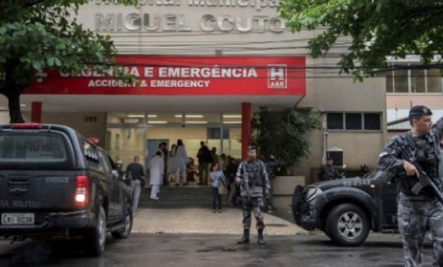 © AFP | Policemen stand guard at the entrance of Miguel Couto Hospital, where a Spanish tourist was taken after being shot by a police