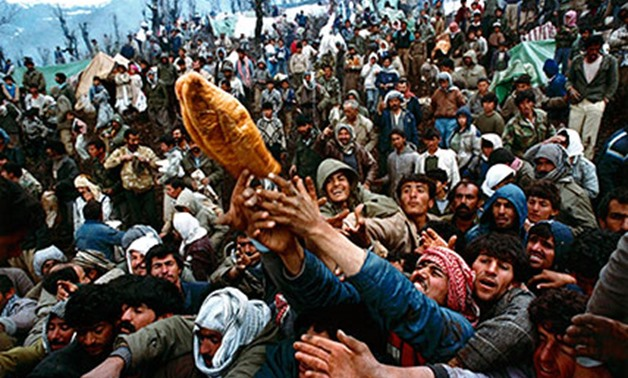By Isabel Coles PAST: Kurdish refugees struggle for a loaf of bread distributed as part of a humanitarian aid effort in 1992. REUTERS/Yannis Behrakis