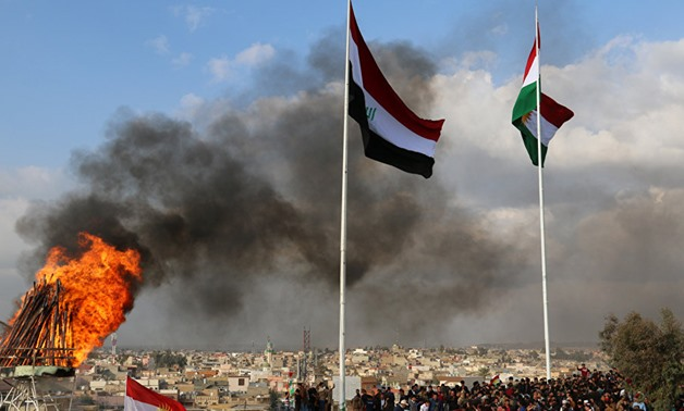Kurdish and Iraqi flags sway in the wind as a bonfire burns during the Nowruz spring festival celebrations in Kirkuk, north of Baghdad. AFP/Marwan Ibrahim