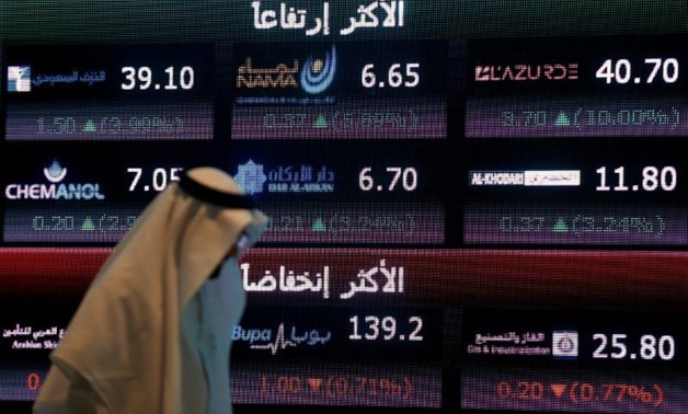 An investor walks past a screen displaying stock information at the Saudi Stock Exchange (Tadawul) in Riyadh, Saudi Arabia June 29, 2016.