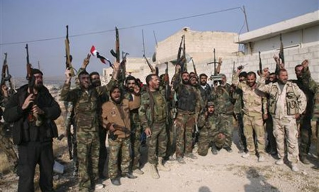 Forces loyal to Syria's President Bashar al-Assad hold up their weapons as they cheer in the town of Safira - REUTERS