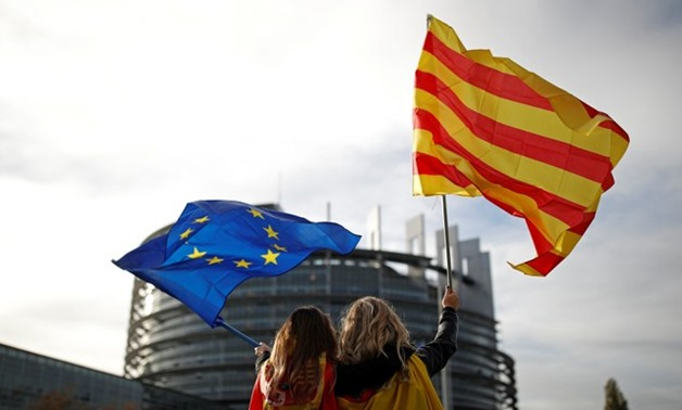 Women hold Spanish and Catalan flags during a gathering against Catalonia independence in front of the European Parliament in Strasbourg - REUTERS