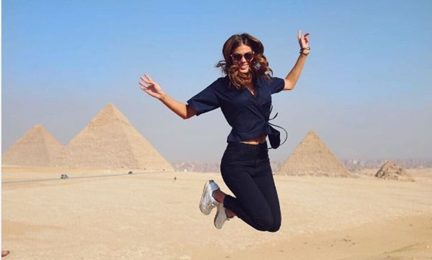 Miss universe cheerfully jumping in front of the Pyramids of Giza – photo from Iris Mittenaere's official Instagram account