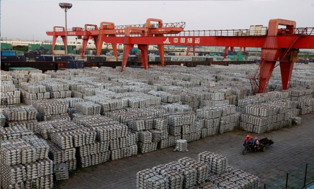 Workers ride on an motor rickshaw through an aluminium ingots depot in Wuxi, Jiangsu province in this September 26, 2012 file picture - REUTERS/Aly Song/File Photo