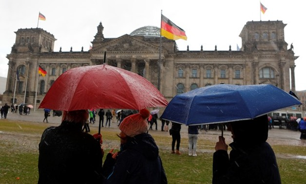 People with umbrellas stand in front of the Reichstag in Berlin, Germany October 29, 2017. REUTERS/Axel Schmidt