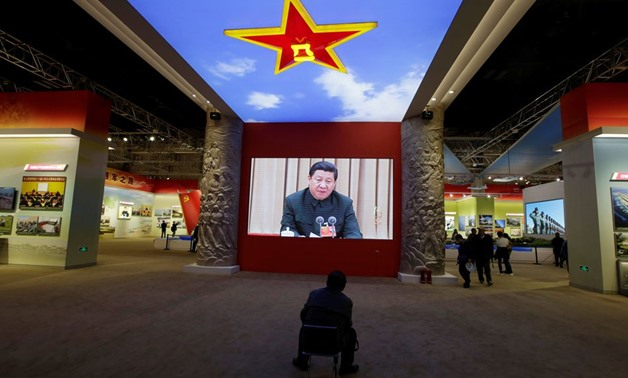 A visitor watches a video showing Chinese President Xi Jinping at a military meeting during an exhibition displaying China's achievements for the past five years. Reuters