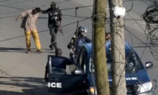 A still image taken from a video shows police arresting a man in the English-speaking city of Buea - REUTERS