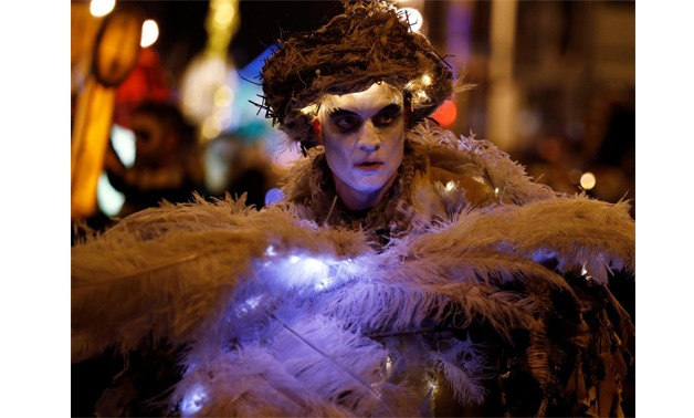 A performer dances during a Halloween lantern carnival in Liverpool, Britain, October 29, 2017 - REUTERS/Phil Noble