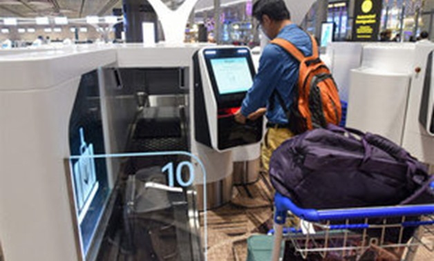 A passenger checks-in his luggage using an automated booth at the newly- opened - AFP