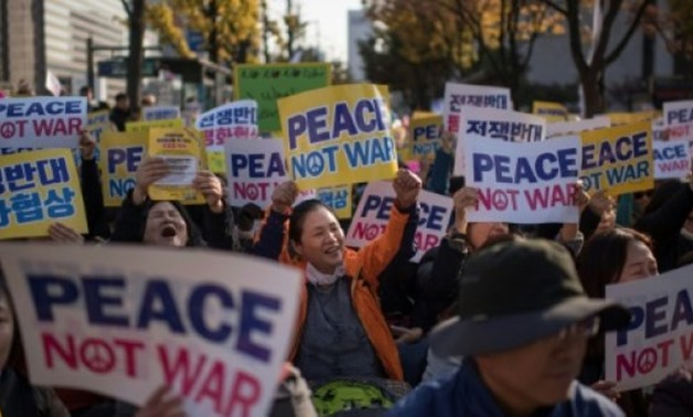 Demonstrators hold placards during a peace rally in Seoul - AFP