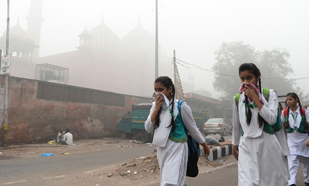Indian schoolchildren cover their faces as they walk to school amid heavy smog in New Delhi on November 8, 2017 - AFP