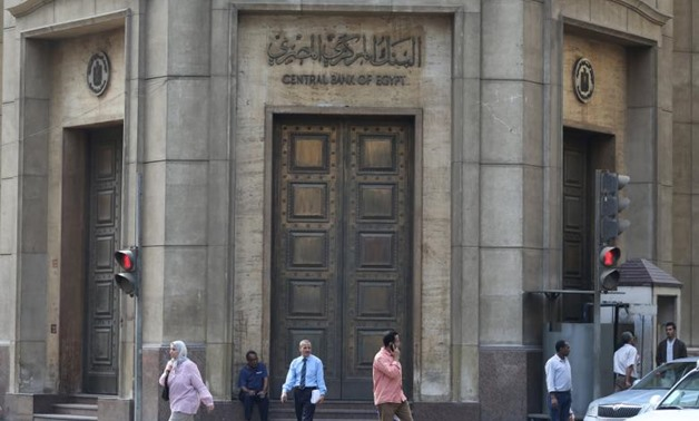 People walk in front of the Central Bank of Egypt's headquarters at downtown Cairo, Egypt - Reuters