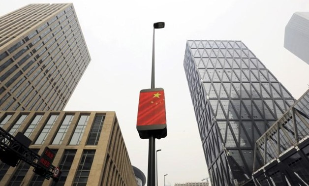 A Chinese national flag is seen among buildings at the Yujiapu financial centre, in Tianjin, China February 22, 2016. REUTERS/Jason Lee