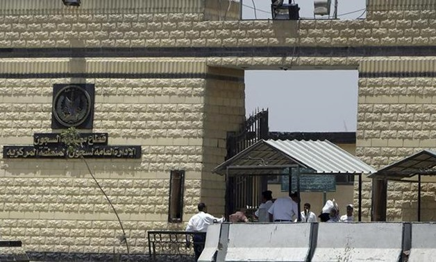 Policemen and people walk in front of the main gate of Tora prison in Cairo. PHOTO: Reuters