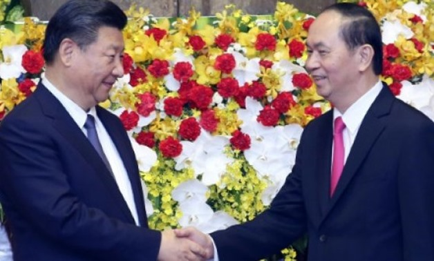 © POOL/AFP | Chinese President Xi Jinping (L) shakes hands with Vietnamese President Tran Dai Quang (R) at the presidential palace in Hanoi