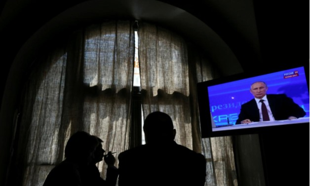People look at a screen at a media centre during Russian President Vladimir Putin's live broadcast nationwide phone-in in Moscow, Russia April 17, 2014 -  REUTERS/Sergei Karpukhin/File Photo