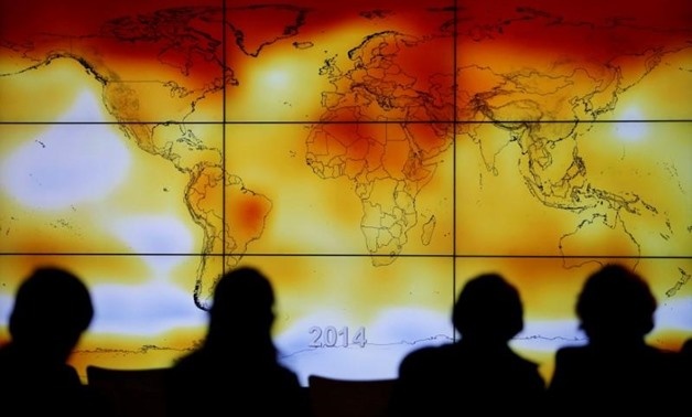 FILE- Participants are seen in silhouette as they look at a screen showing a world map with climate anomalies during the World Climate Change Conference 2015 (COP21) at Le Bourget, near Paris, France, December 8, 2015. REUTERS/Stephane Mahe/File Photo