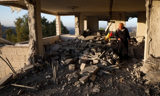 A man looks at the remains of the house of Palestinian assailant Nemr al-Jamal after it was destroyed by Israeli troops in the West Bank village of Beit Surik near Jerusalem November 15, 2017 - REUTERS/Mohamad Torokman